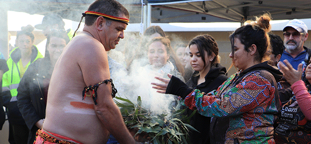 Image of an Aboriginal man and woman with burning leaves at 2018 NAIDOC week march