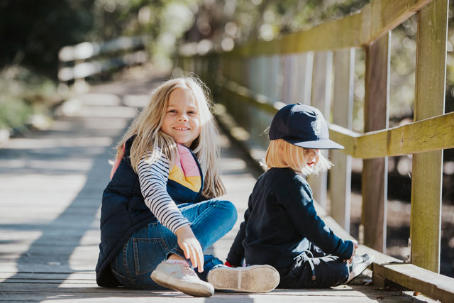 Young girl and boy sitting on boardwalk playing