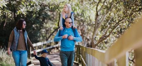 Family of 4 walking along Tanilba Boardwalk