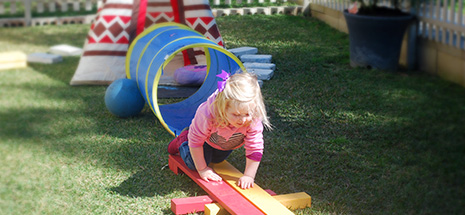 Little girl playing on obstacle course