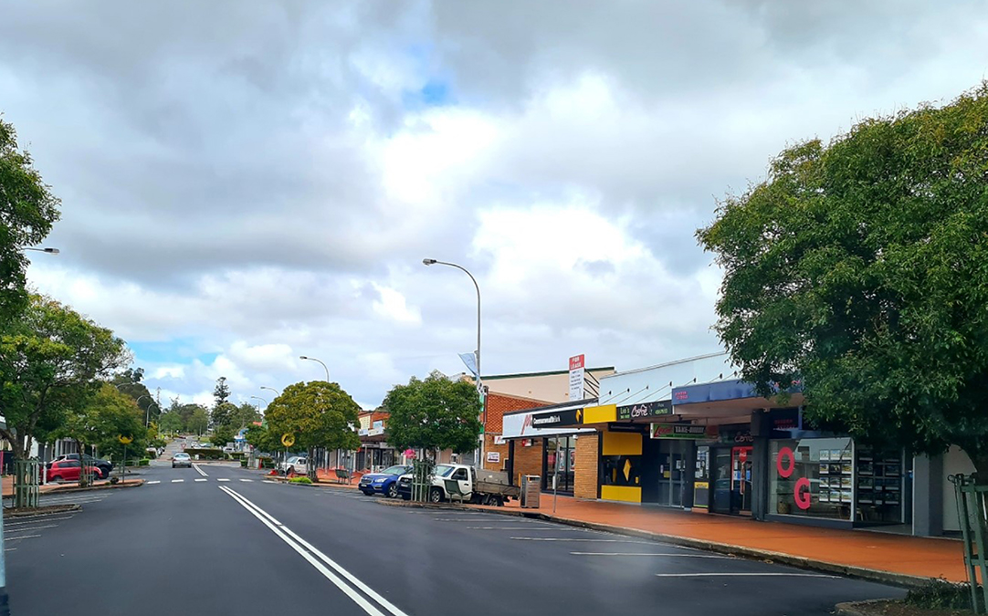 View up William Street towards Adelaide Street in Raymond Terrace. Resurfaced road is black with fresh white painted line marking.