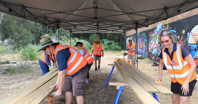 Volunteers of the 7 Day Makeover at Anna Bay sanding lengths of timber