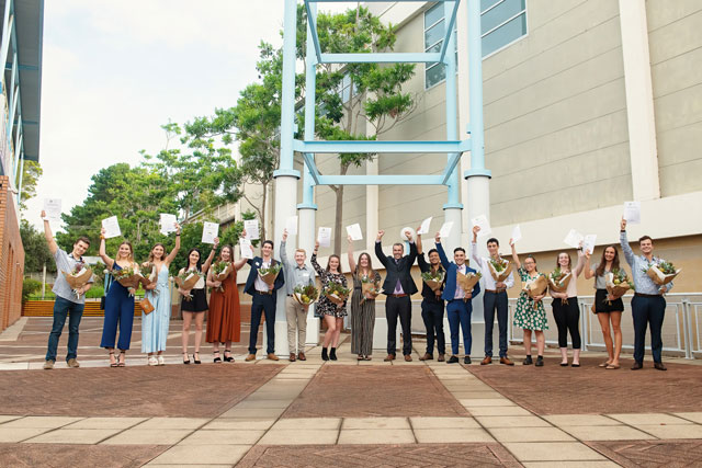 The 18 winners of the 2020 Mayoral Academic Scholarship Program standing outside the Council chambers holding up their certificates.