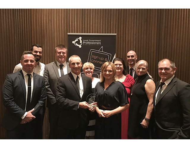 General Manager and team hold the award