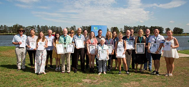 All of the Annual Award winners together holding their certificates by the river