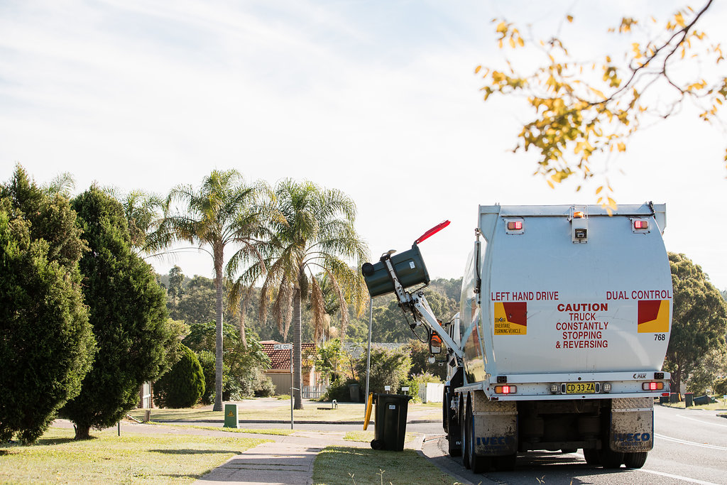 Pictured: Back of a garbage truck on the side of a tree-lined street. The truck is using a mechanical arm to lift a red bin. A yellow bin sits on the kerbside.