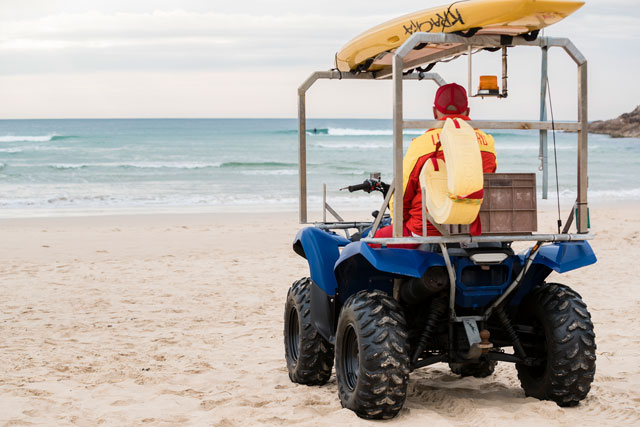 Lifeguard Phil Rock in a buggy looking out over One Mile Beach