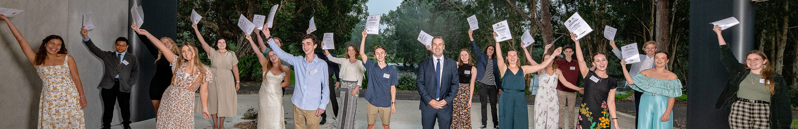 Image of our 20 scholarship recipients holding their certificates in the air and smiling, with Mayor Ryan Palmer in the centre