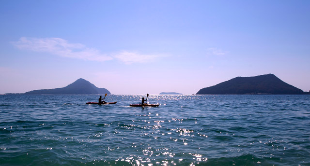 2 kayakers paddling across the sparkling water with mountains in the background