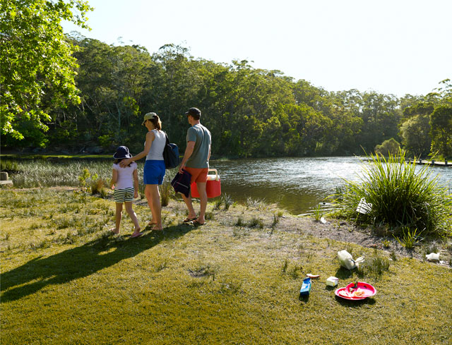 A family walk away from their picnic leaving their rubbish behind