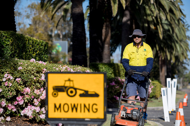 Council worker mowing median strip on a sunny day with large reflective mowing sign in foreground