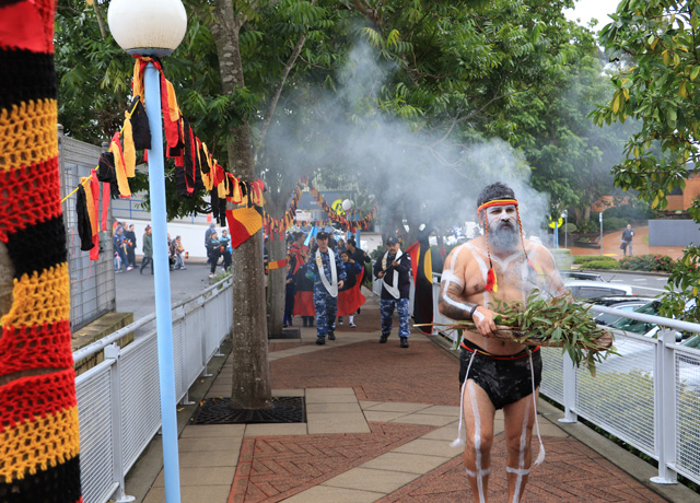 Aboriginal man in traditional dress with smoking plants leads the march for NAIDOC Week