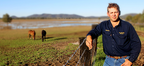 Farmer standing by fence